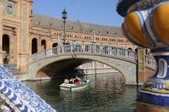 Boat passing under nice bridge. In the pond of the Plaza de Espana of the city of Seville, Andalusia Spain Royalty Free Stock Photos