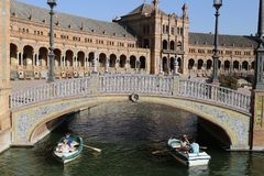 Boat passing under nice bridge. In the pond of the Plaza de Espana of the city of Seville, Andalusia Spain Stock Photos