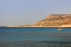 Boat and Peninsula at Cape Greco Cyprus. Under a Cloudless Sky with a Yellow Rocky Headland in the Background Stock Images