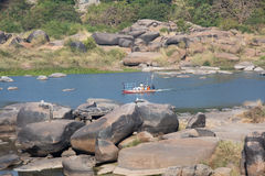 A boat with people sailing along the river. A boat with people floating in the middle of a river between large stones Stock Photos