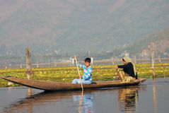 Boat people, Srinagar, Kashmir, India. A Kashmirian woman and son are heading for the boat market on Dal lake Stock Photography