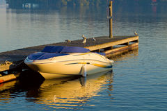 Boat at a Pier on Autumn Morning. Autumn morning lake with a motor boat at a pier royalty free stock photos