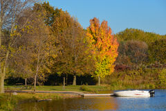 Boat at a Pier during autumn. This is a motor boat at a wooden pier at Coon Rapids Dam Regional Park in Minnesota during autumn Royalty Free Stock Photos