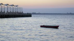 Boat, pier. A generic dingy, or small boat, sits in the water near a pier. Twilight or dusk Stock Image
