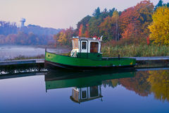 Boat at a Pier on a Misty Autumn Morning. Misty morning lake with a motor boat at a pier and colourful forest on a background Stock Photo