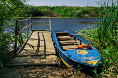 Boat at the pier on the pond. Boat at the pier on the picturesque pond Stock Photos