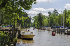 Boat in pier, and several canoes rowing along canal in Tigre, Buenos Aires Stock Photo