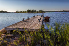 Boat and pier. A small boat tied up to a pier in Sweden during the Summer stock photos