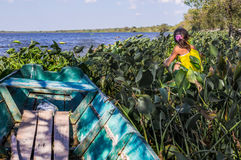 Boat with plants and girl. Puerto Pollo, Paraguay on August 8, 2015: An indigenous girl sitting next to a small fishermen's boat in Puerto Pollo at Rio Paraguay Royalty Free Stock Photo