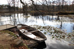 Boat and pond in the autumn forest. Vivid cover of leaves and boat in the autumn park Stock Photo
