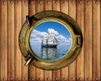Boat porthole window ship with ocean view and wood background.  .