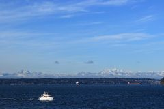 Boat in the Puget Sound. A boat moving through the Puget Sound with the Cascade Mountains in the background Royalty Free Stock Photos