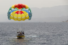 A Boat Pulls Colorful Para Sailing At The Blue Sea. Eilat 2017. Royalty Free Stock Images