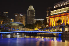 Boat Quay. Singapore Boat Quay at night with the blue illuminated Cavenagh Bridge, one of the esplanade domes (left, backgr.), the cityscape of Marina Bay and a Royalty Free Stock Photo