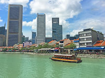Boat Quay and Singapore River, Downtown Singapore. A tour boat traverses the Singapore River past Boat Quay in downtown Singapore royalty free stock photography