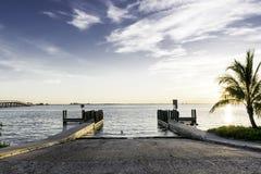 Boat Ramp At Sunrise. Located at Sanibel Island, Florida - USA. Sun rising at the horizon with palm tree Royalty Free Stock Photos