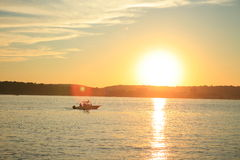 Boat in the rays of sunset. On the lake stock images