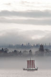 Boat with red stripes sailing in a heavy mist Stock Images
