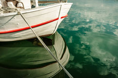 Boat reflection on green water in harbor Stock Photography