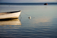 Boat Reflections. A small boat tied down in a calm bay at dusk Royalty Free Stock Photo