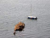 The boat and the remains of the old ship. Stock Image
