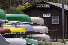 Boat Rentals. Stack of boats next to a rental building selling worms for fishing Royalty Free Stock Photos