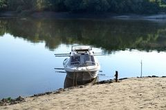 The boat resting ashore. After several hours of fishing boat and fishermen are resting. The sand is hot stock photo