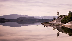 Boat resting at the bank of a fjord in Norway Royalty Free Stock Images