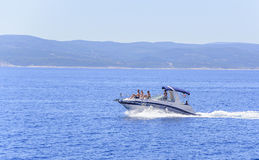 The boat with the resting people is moving quickly on the sea waves. Royalty Free Stock Photo