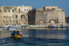 Boat returns to port with the castle. In salento - Italy Stock Photography