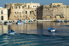 Boat returns to port with the castle. In salento - Italy Royalty Free Stock Images