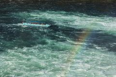 Boat on the Rhine river just below the Rhine Falls. Laufen, Switzerland - 17 October, 2017: a boat on the Rhine river just below the Rhine Falls, rainbow above Stock Photos