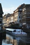 Boat on the Rhine of Strasbourg. A boat sailing through the narrow channel of the river, in La Petite France, which is a historic quarter of Strasbourg Stock Image