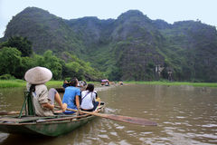 Boat Ride in Rural Vietnam. A beautiful view of the imposing rocks towering above tourists on a boat ride through Tam Coc, Vietnam Royalty Free Stock Photo