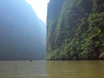A boat rides down the Sumidero Canyon as sunlight bursts through in the morning in Chiapas State stock photos