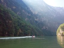 A boat rides down the Sumidero Canyon as sunlight bursts through in the morning in Chiapas State stock photography