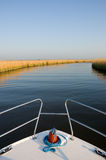 Boat on a River. White motor boat travelling along a calm stretch of blue water between reeds under a clear blue sky royalty free stock photos