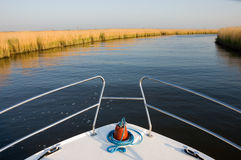 Boat on a River. Bow of a white boat cruising along a calm blue river past golden yellow reed-beds looking towards the distant horizon stock photos