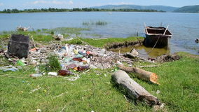 Boat by the river bank full of garbage stock video