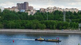 The boat is on the river in the city. The boat is crossing the river in Moscow city stock footage