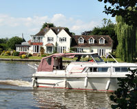 Boat on the River Thames. Boat passing a large Riverside House on the River Thames in England Stock Photography
