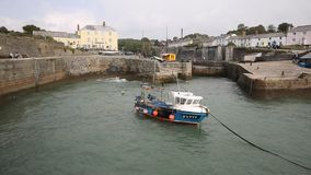 Boat rocking on waves in harbour Charlestown Cornwall England UK near St Austell PAN stock footage