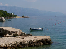Boat at the rocky pier in Croatia. With a view to the seashore Stock Photos