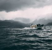 Boat in rocky waters on lake royalty free stock photography