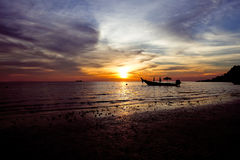 Boat in a romantic beach at sunset. Beautiful tranquil romantic beach with a boat silhouette in sunset Royalty Free Stock Images