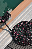 Boat rope on dock. Rope of boat twist on dock board, as a circle, shown as maritime activities, sport or entertainment on sea Royalty Free Stock Photo