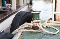 Boat rope tied to the old iron cleats Royalty Free Stock Photos