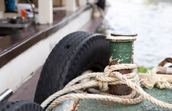 Boat rope tied to the old iron cleats Stock Photography