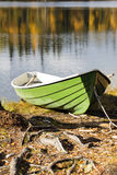 Boat at rough by tree roots shore Stock Photos