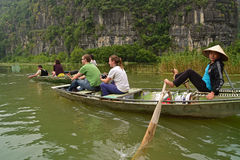 Boat rower looking at the camera while rowing using feet for her tourist customers Stock Images